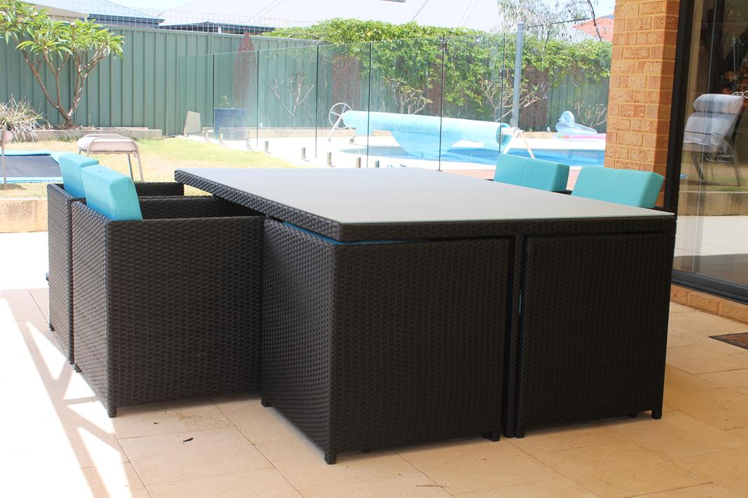 A black rattan setting with 10 chairs, on the patio.