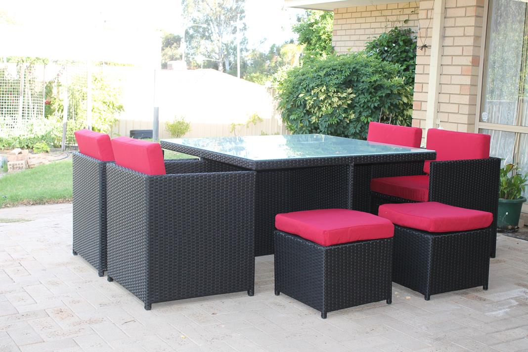 An outdoor dining setting with black wicker and red fabric. On the patio of a Perth home.