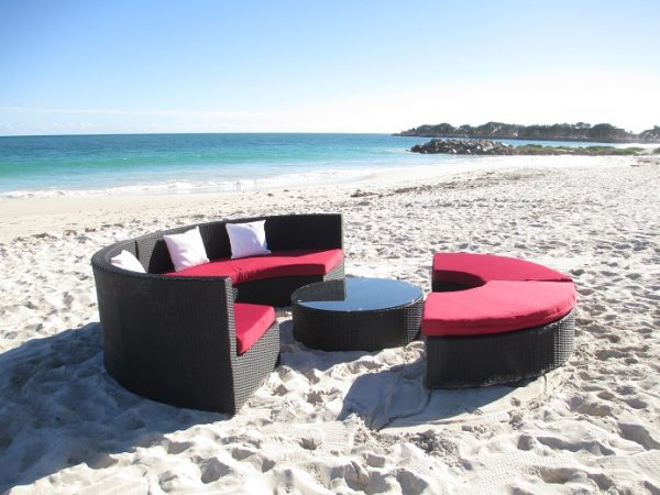 A black wicker lounge set that is round.