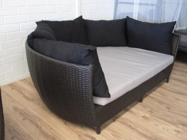 A large day bed for the balcony with puffy back rest cushions.
