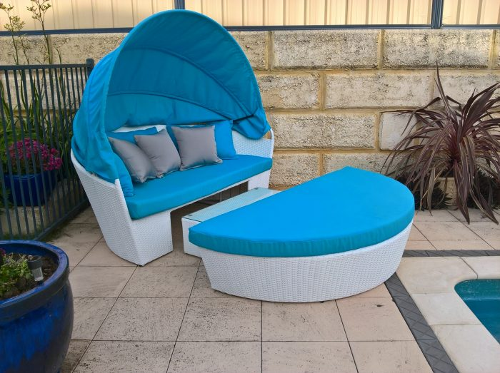 A beautiful blue fabric day bed with white wicker by the pool