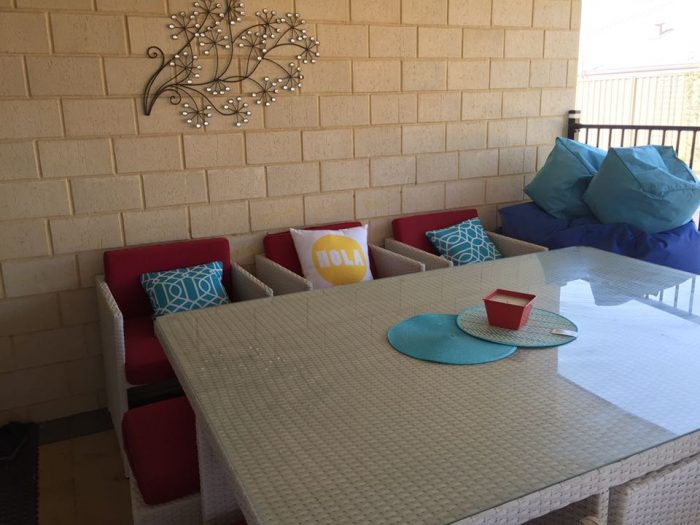White wicker 10 seat outdoor dining setting.