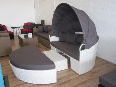 Day bed for lounging outside made of white wicker or rattan with removable canopy.