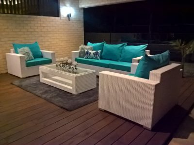 All weather wicker outdoor lounge setting. White furniture is modern and looks beautiful on a dark brown patio. Blue all-weather polyester fabric.