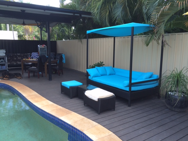 Outdoor Lounge Setting By the Pool. A large day bed with blue fabric.