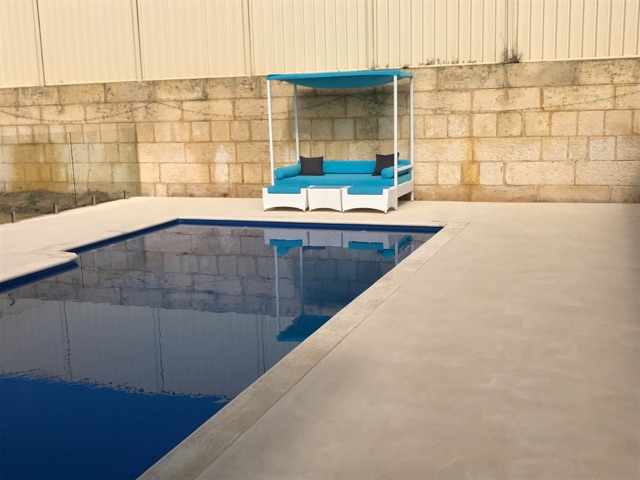Outdoor Day Bed by the Poolside with White wicker and Blue Fabric