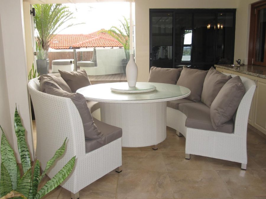 White wicker round dining set with bench style seats and a Lazy Susan.