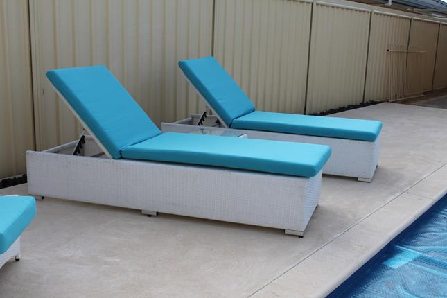 Two beautiful sunbeds with a coffee table in the middle. Made of all-weather white rattan, with blue fabric.